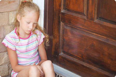 Image of young girl sitting outside her house on by the front door looking sad.